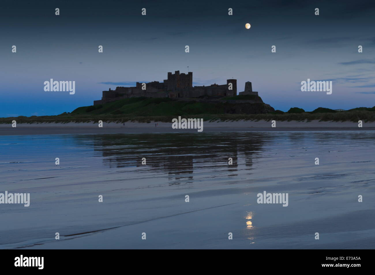 Bamburgh Castle under a full moon at dusk in summer, Bamburgh, Northumberland, England, United Kingdom, Europe - Stock Image