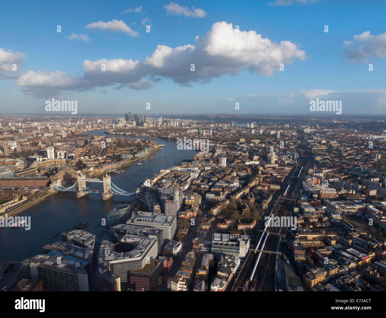 Aerial cityscape showing River Thames, Tower Bridge and railway tracks, London, England, United Kingdom, Europe - Stock Image