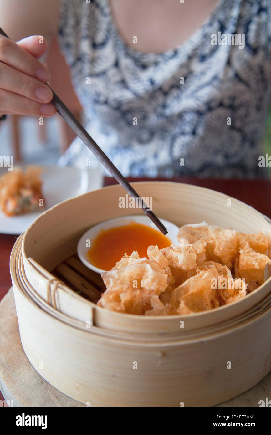 Woman eating prawn wrapped in fried rice paper at The Waterfront restaurant, Da Nang, Vietnam, Indochina, Southeast - Stock Image