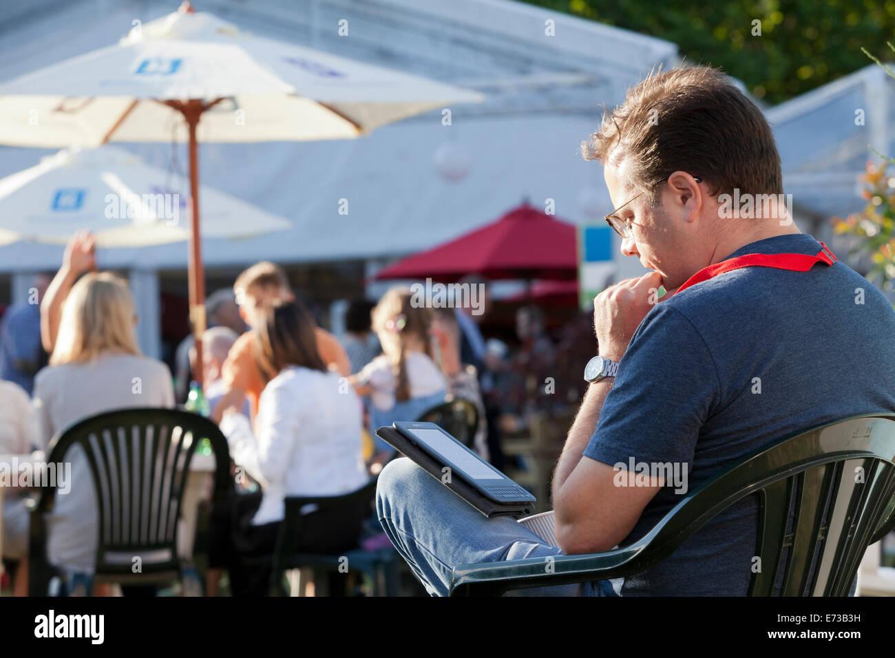 A visitor reads an e-book on the opening day of the Edinburgh International Book Festival 2014. Edinburgh, Scotland. - Stock Image