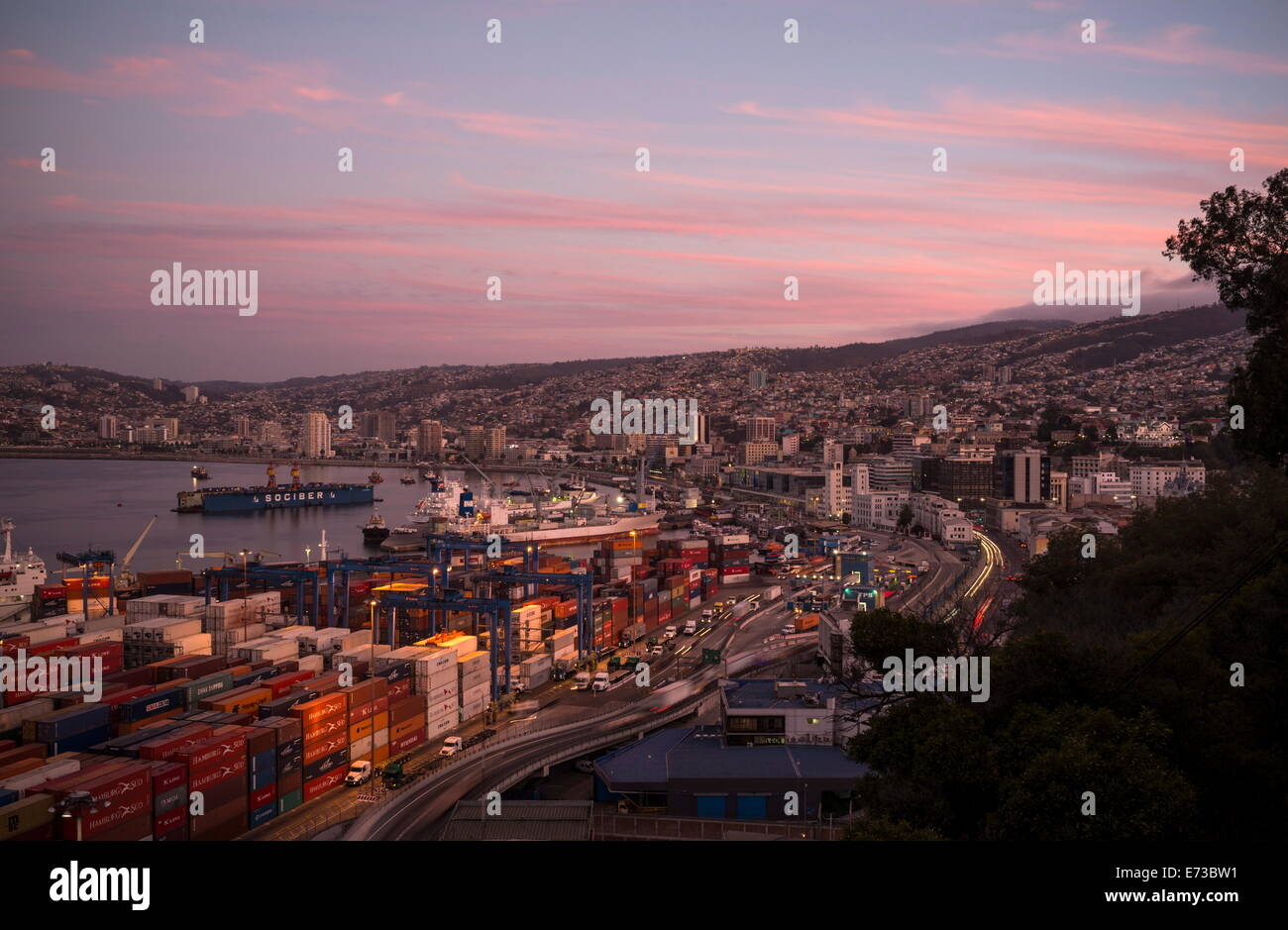 View of city and ports at dusk from Paseo 21 de Mayo, Cerro Playa Ancha, Valparaiso, Central Coast, Chile, South - Stock Image