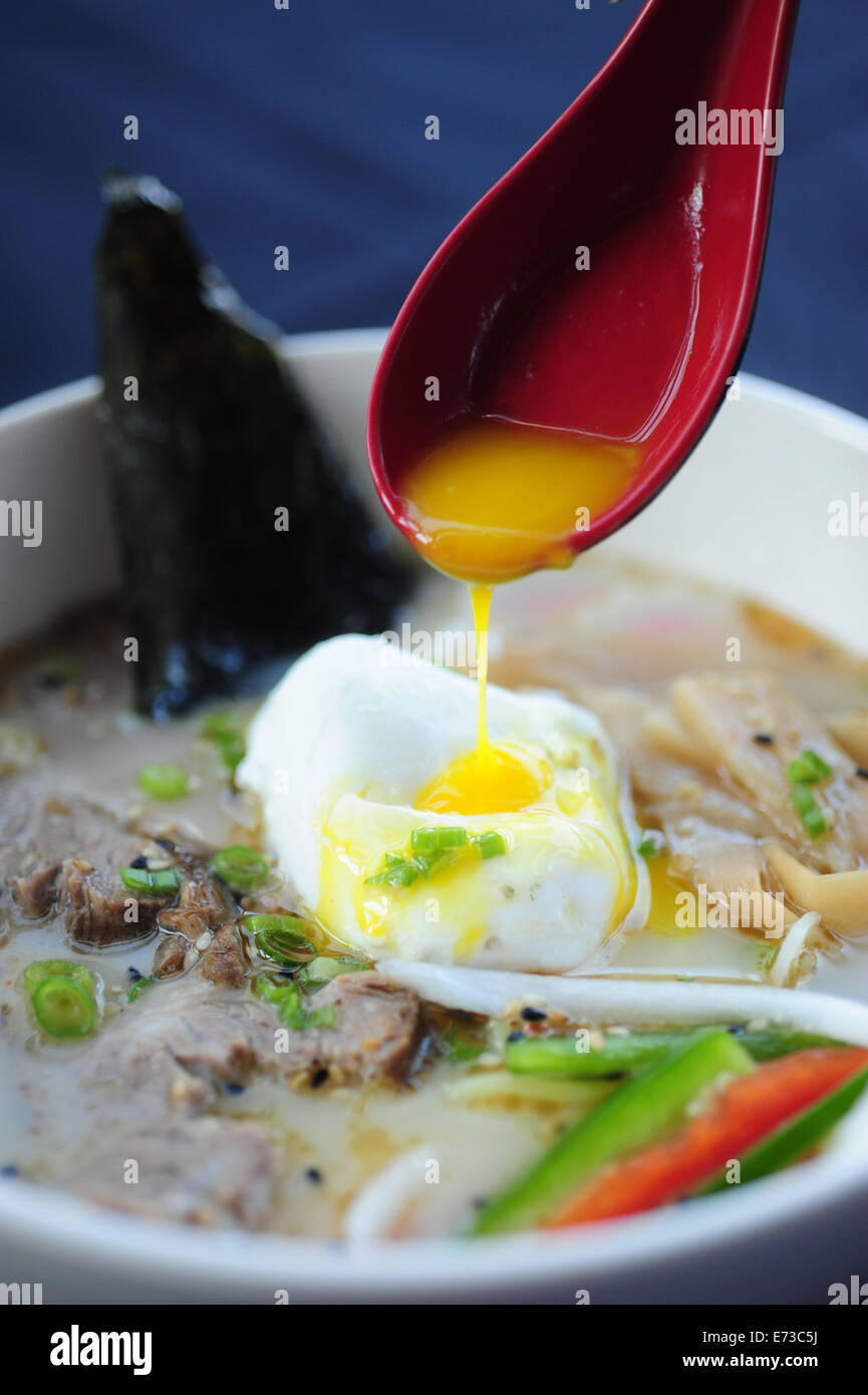 Food Dining Asian Japanese ramen noodle soup with an poached egg hand holding red spoon - Stock Image