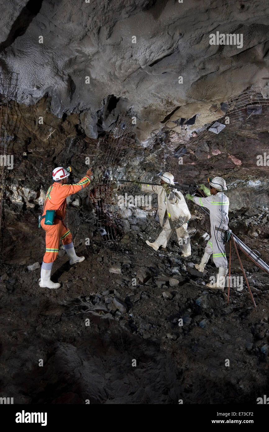 Drilling holes for steel mesh safety support before cementing and blasting again inside new platinum mine portal. - Stock Image