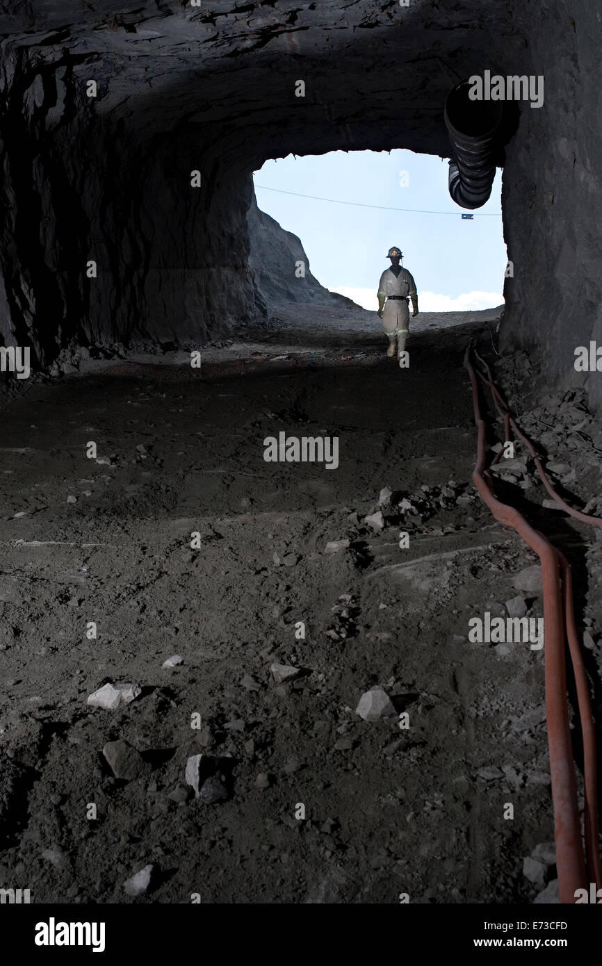 African miner walking down slope to check access into new underground platinum mine from entrance portal. South - Stock Image