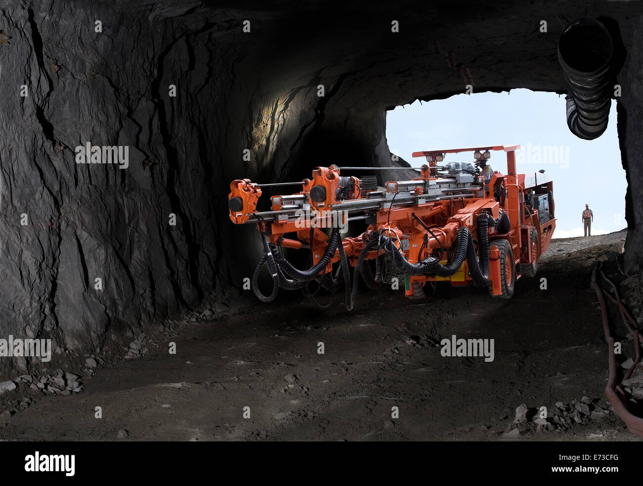 Drill rig moving down into platinum mine from entrance portal before drilling blast holes in rock for new service - Stock Image
