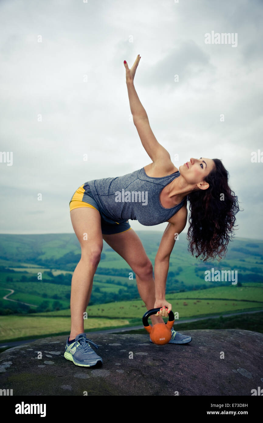 Female exercising outdoor with kettlebells - Stock Image