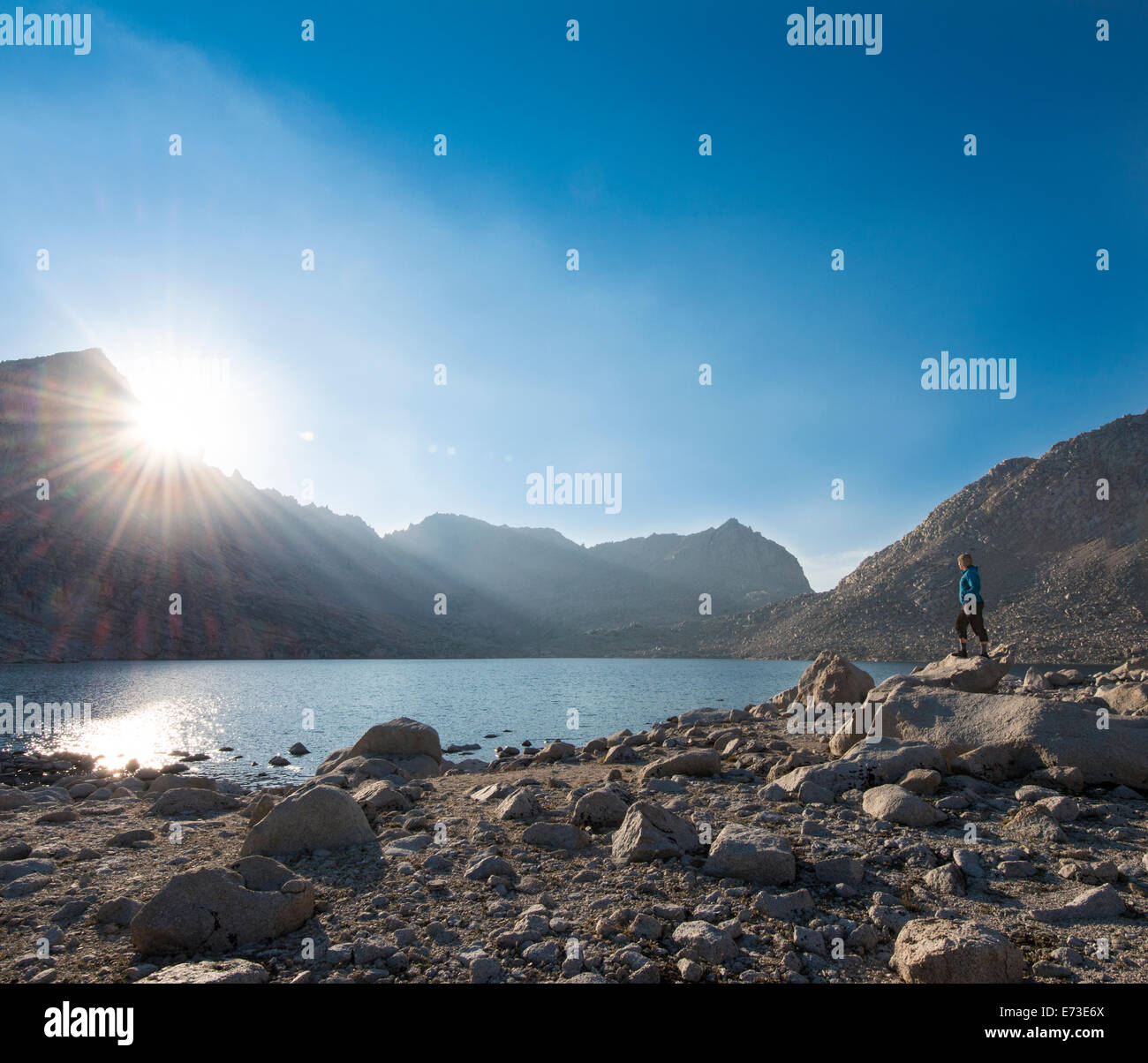 Sunstar and hiker looking over Royce Lakes, High Sierra - Stock Image