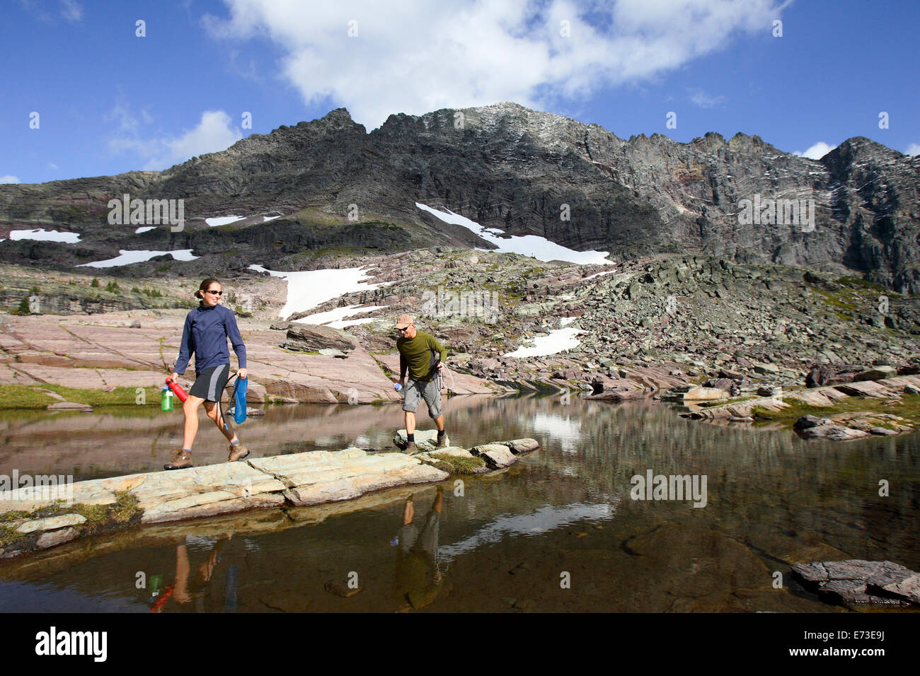 A man and woman filter water in Glacier National Park, Montana. - Stock Image