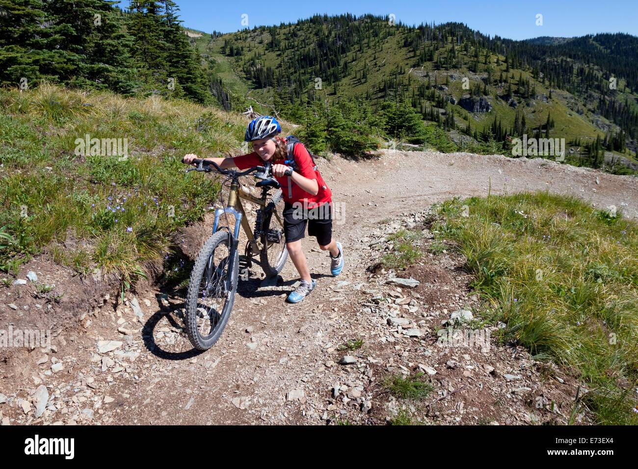 A teenage girl pushes her mountain bike in Whitefish, Montana. Stock Photo