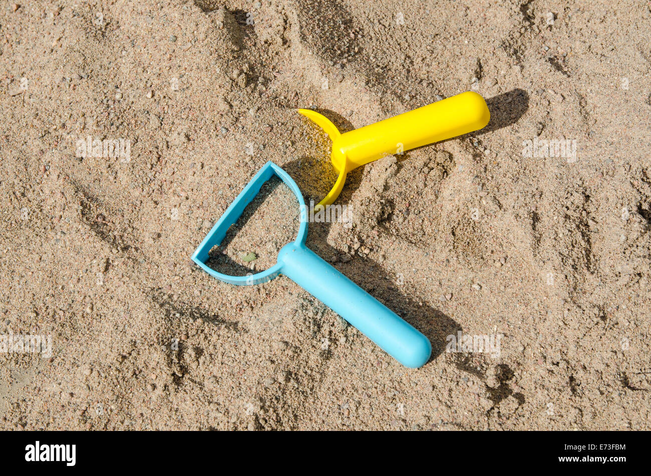 Closeup of plastic toys in a sandbox - conceptual sandbox level - Stock Image