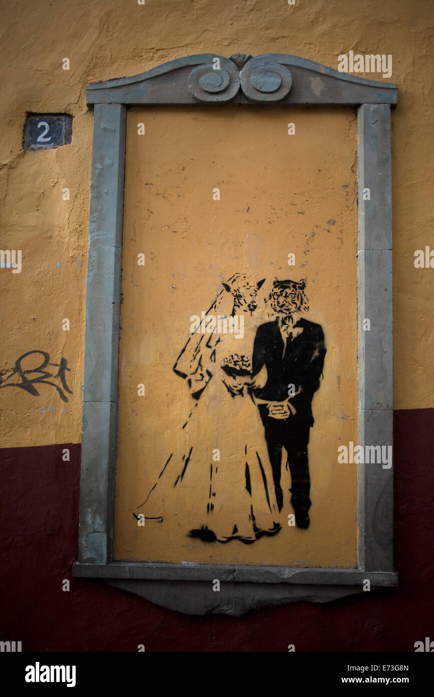 A graffiti showing a wedding between a she-wolf and a tiger decorates a sealed window in Guanajuato, Mexico, July - Stock Image
