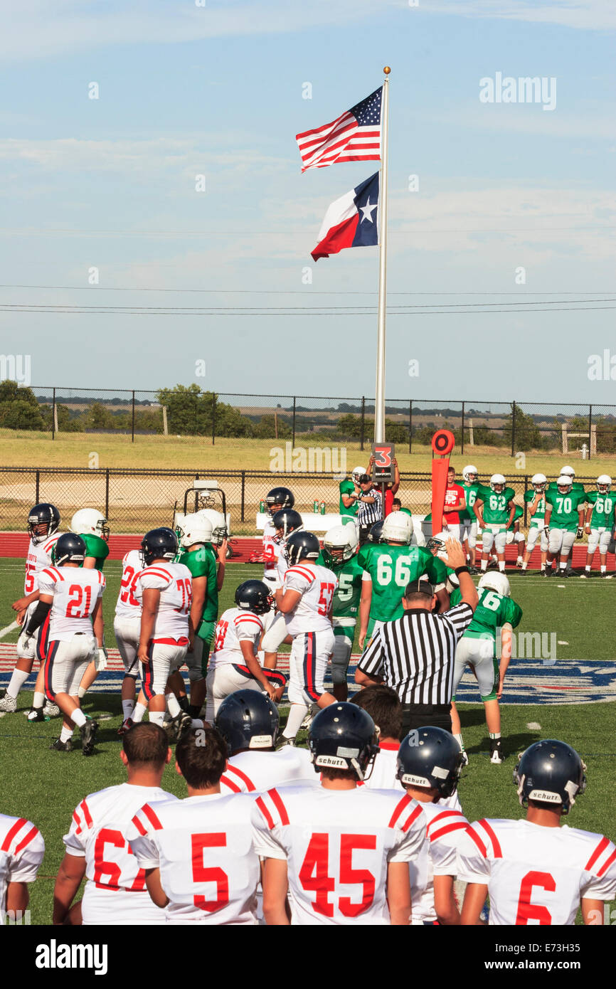 High school junior varsity football game being  played under US and Texas flags - Stock Image