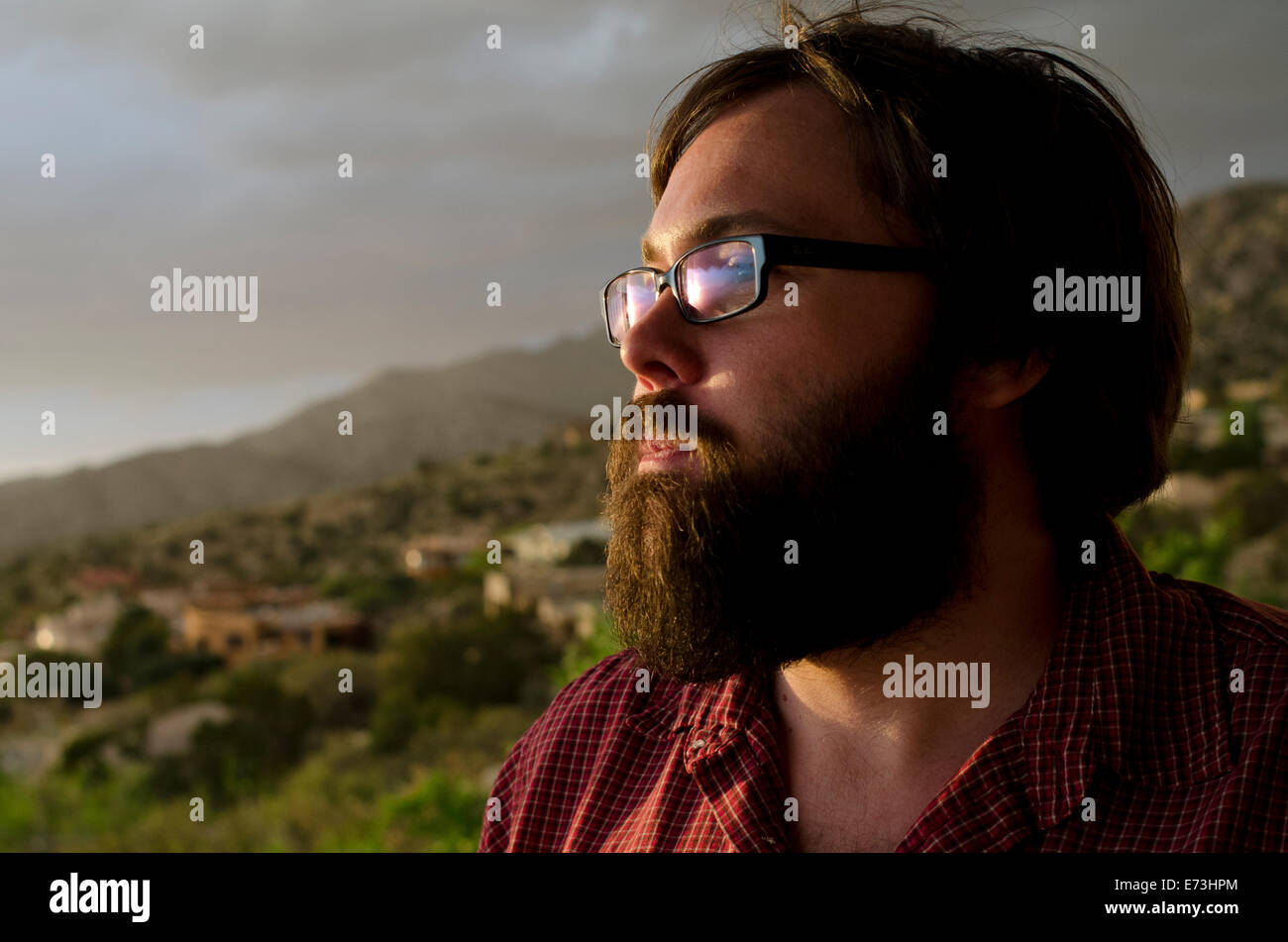 A man in his late twenties, takes in the view overlooking the city of Albuquerque, New Mexico. - Stock Image