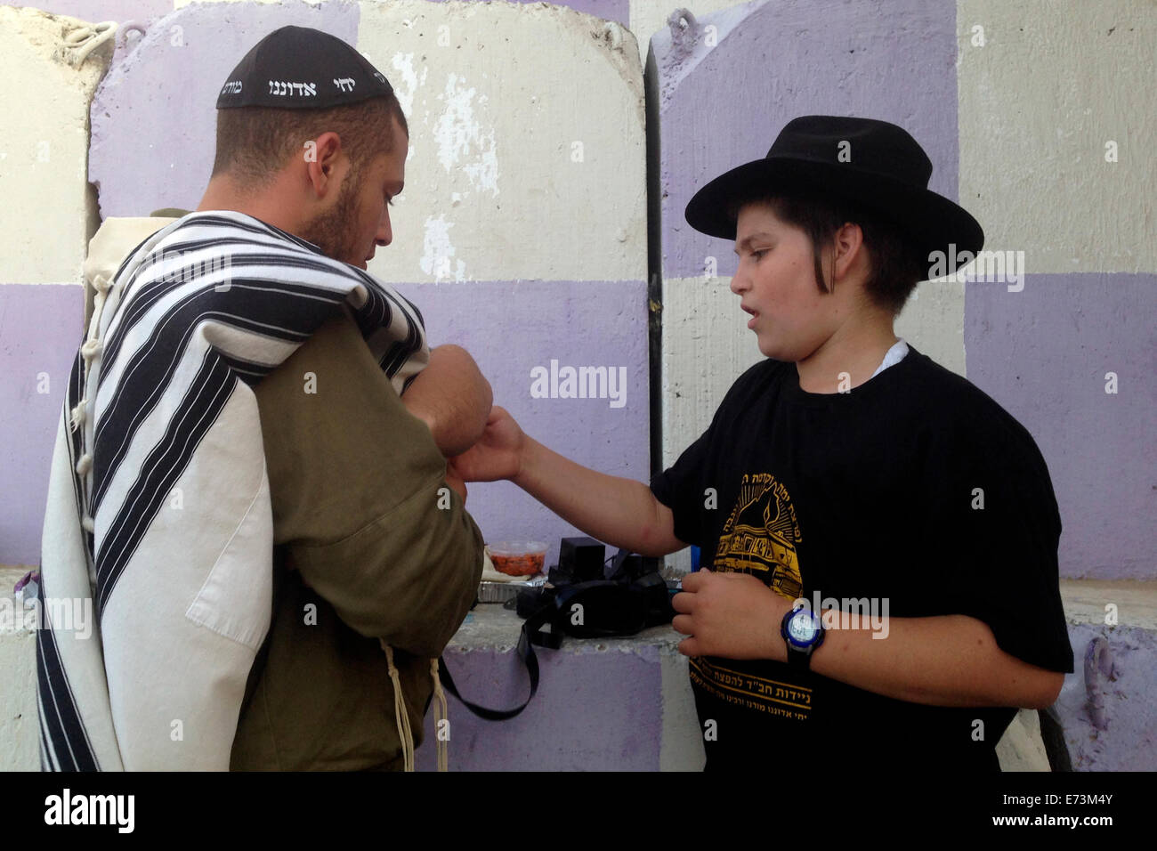 A member of Habad religious movement helps an Israeli soldier to put traditional Tfilin Israel - Stock Image