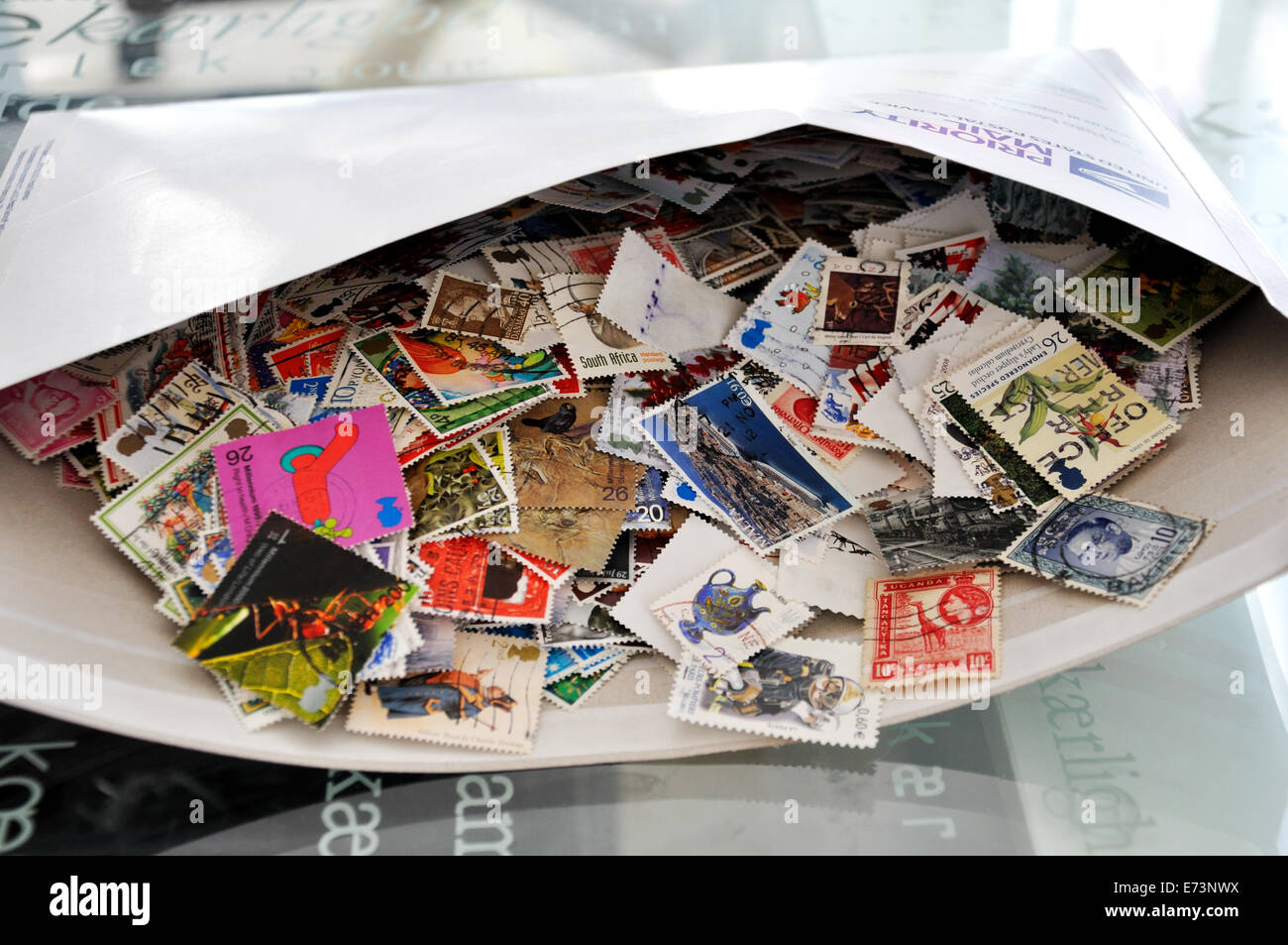 Envelope full of used postage stamps - Stock Image