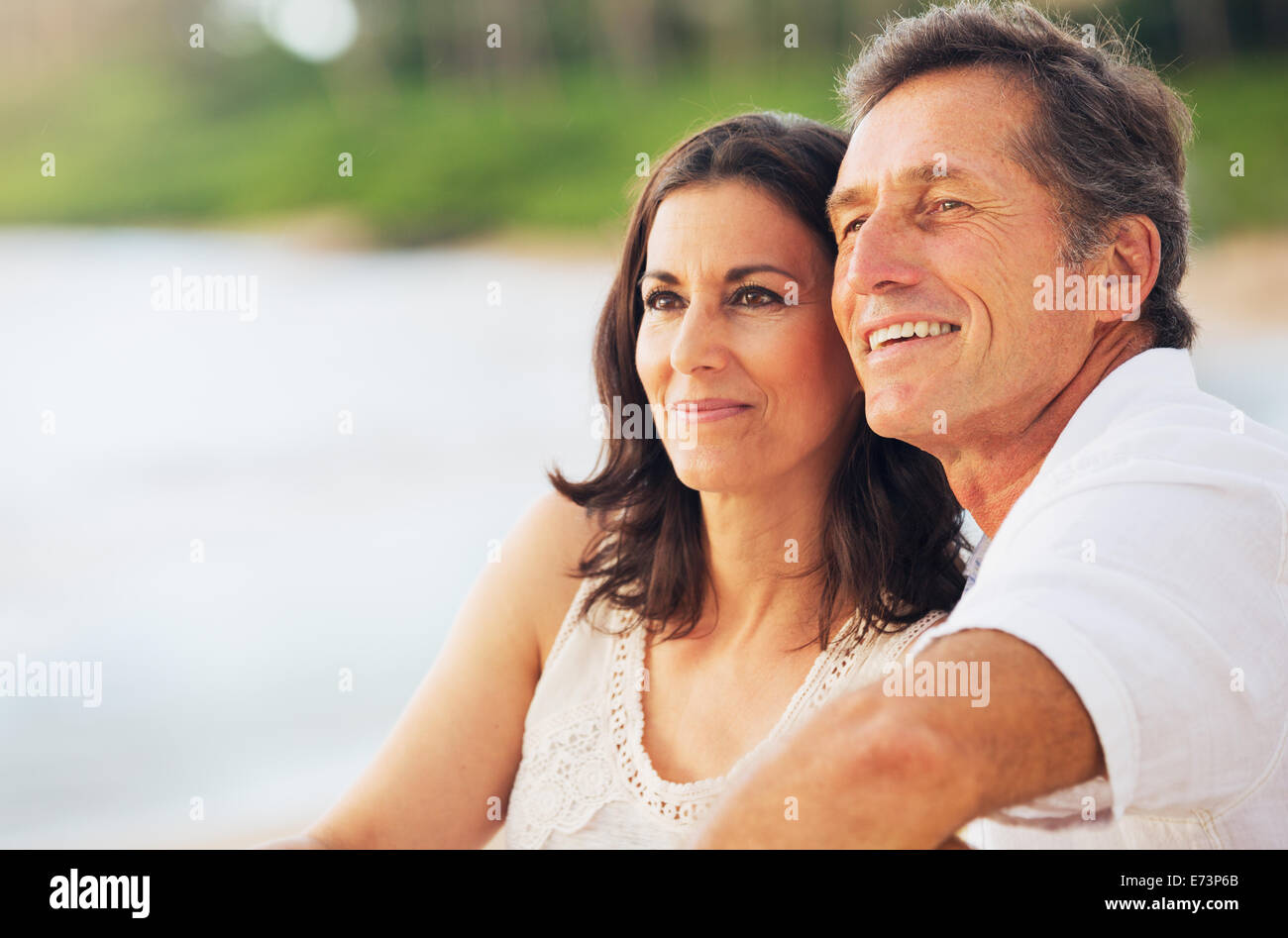 Happy Romantic Mature Couple Enjoying Sunset on the Beach - Stock Image