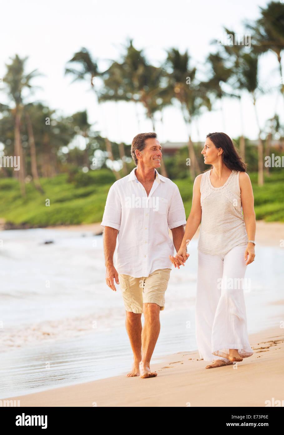 Romantic Mature Couple Enjoying Walk on the Beach - Stock Image