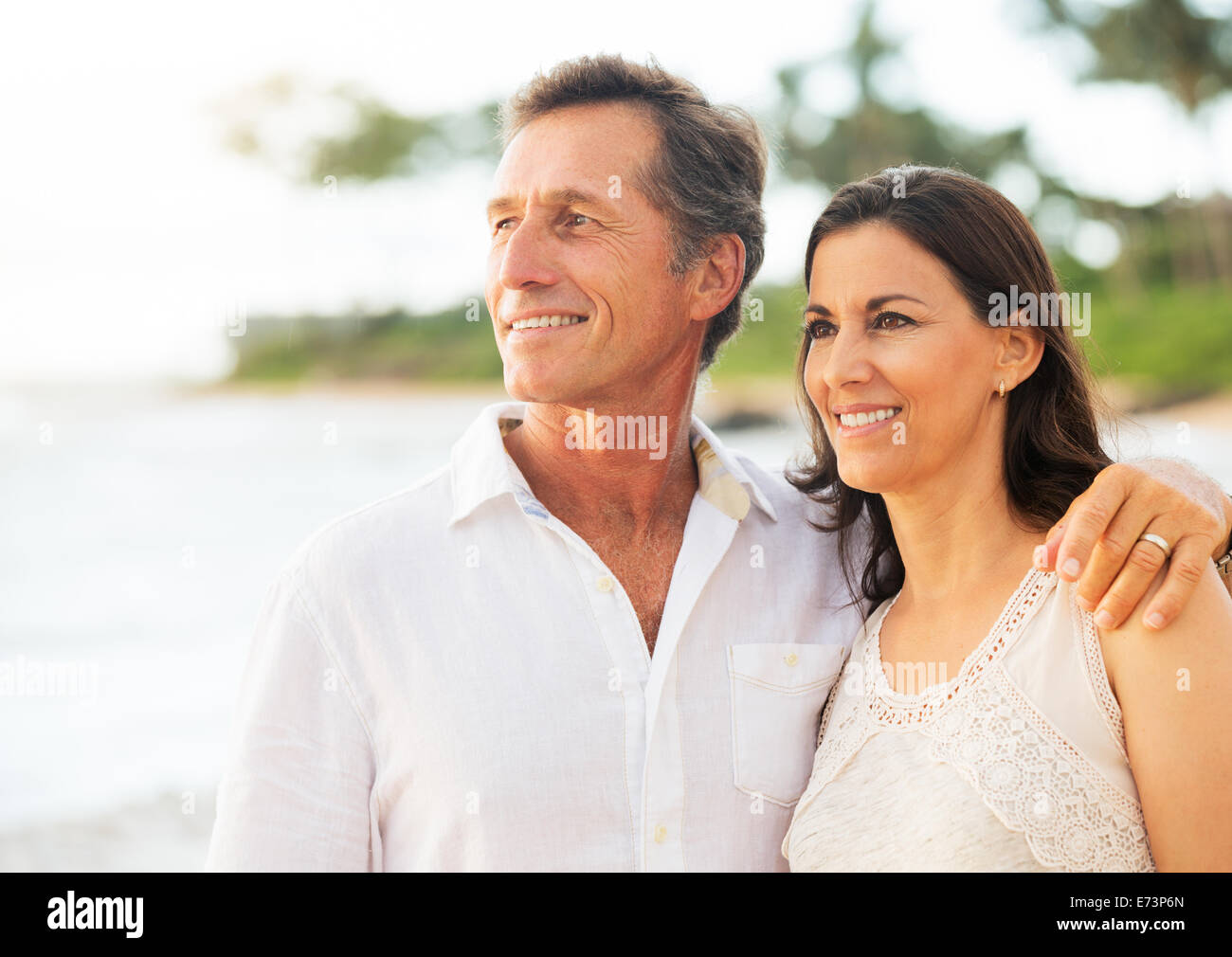 Mature Retired Couple Enjoying Tropical Sunset Beach Vacation - Stock Image