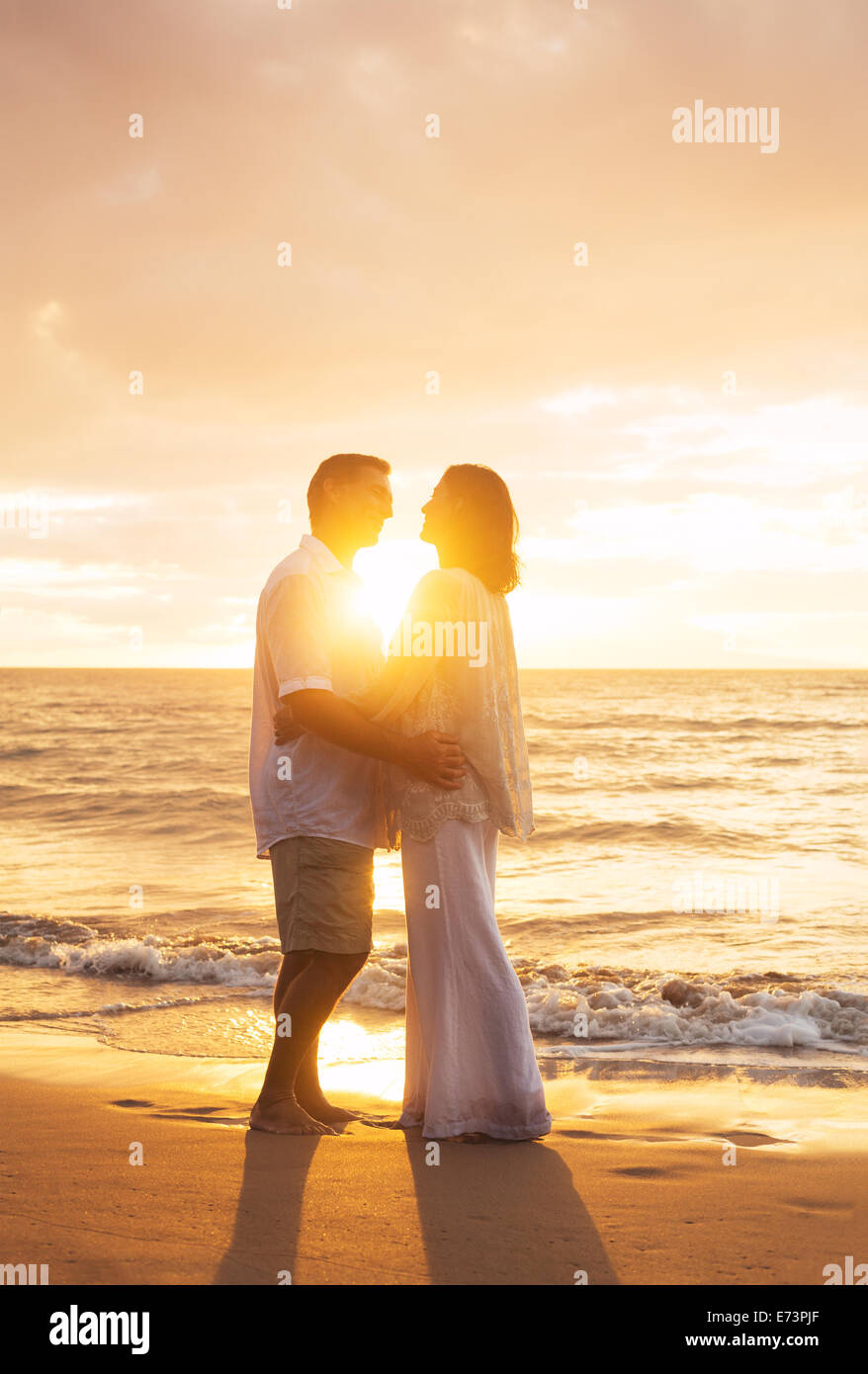 Romantic Mature Couple Kissing at Sunset on the Beach - Stock Image