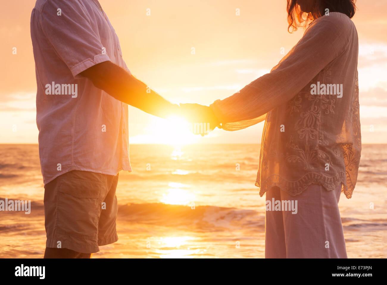 Romantic Mature Senior Couple Holding Hands Enjoying at Sunset on the Beach - Stock Image