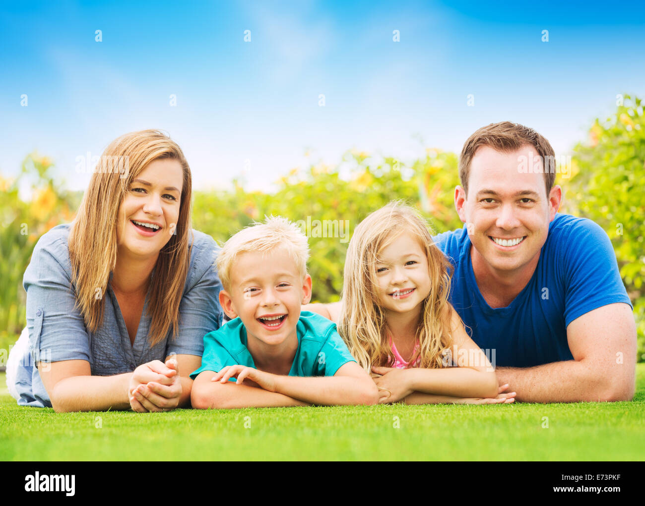Portrait of Happy Family Outside on Grass - Stock Image