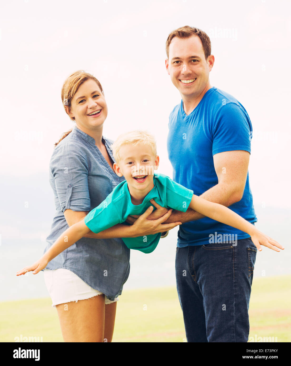 Happy Family Outside Playing Airplane with Young Son - Stock Image