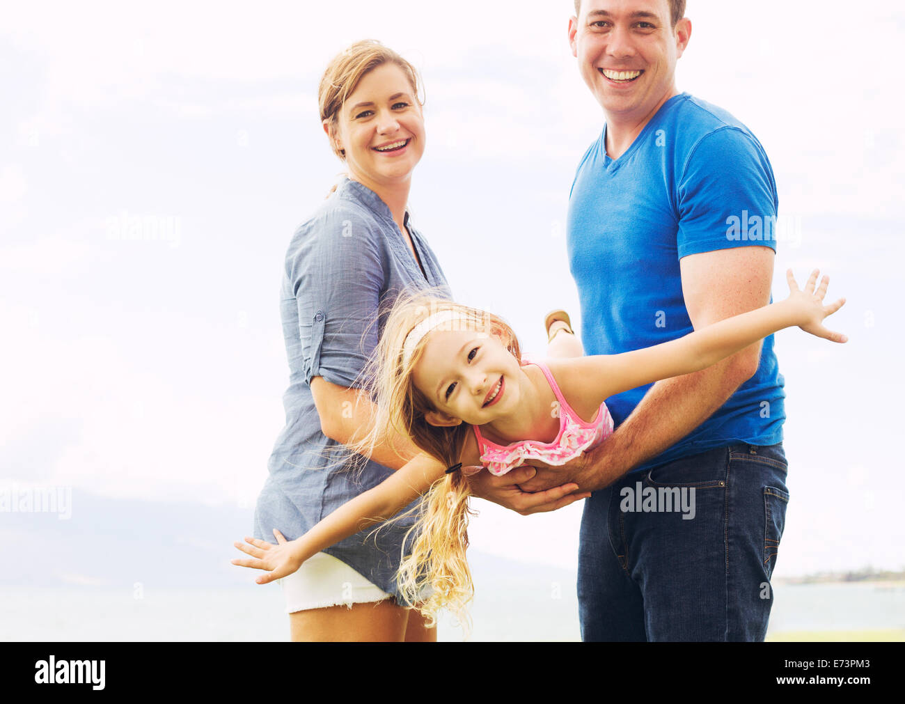 Happy Family Outside Playing Airplane with Young Daughter - Stock Image