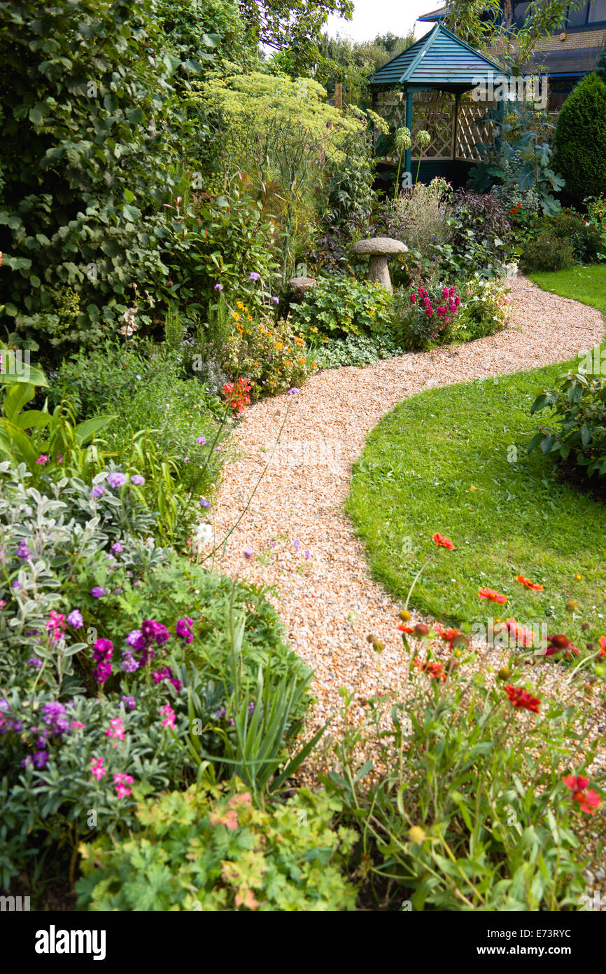 English Cottage Garden Winding Shingle Path Leading To A Gazebo Between Grass Lawn And Flowerbed Of Mixed Plant Varieties