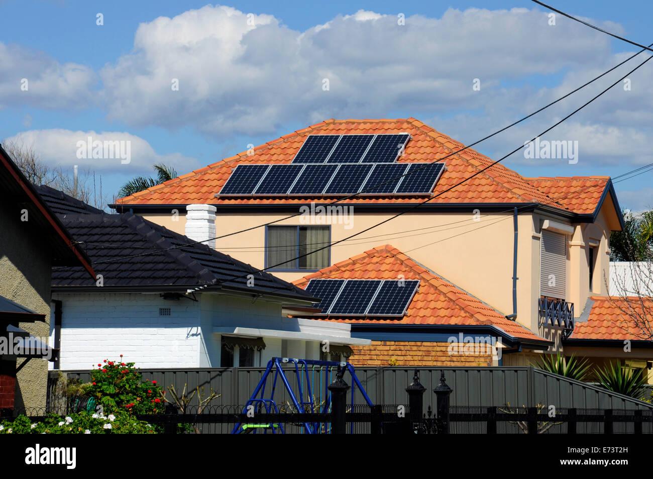 Australian photovoltaic solar power panels on suburban house roof top. - Stock Image