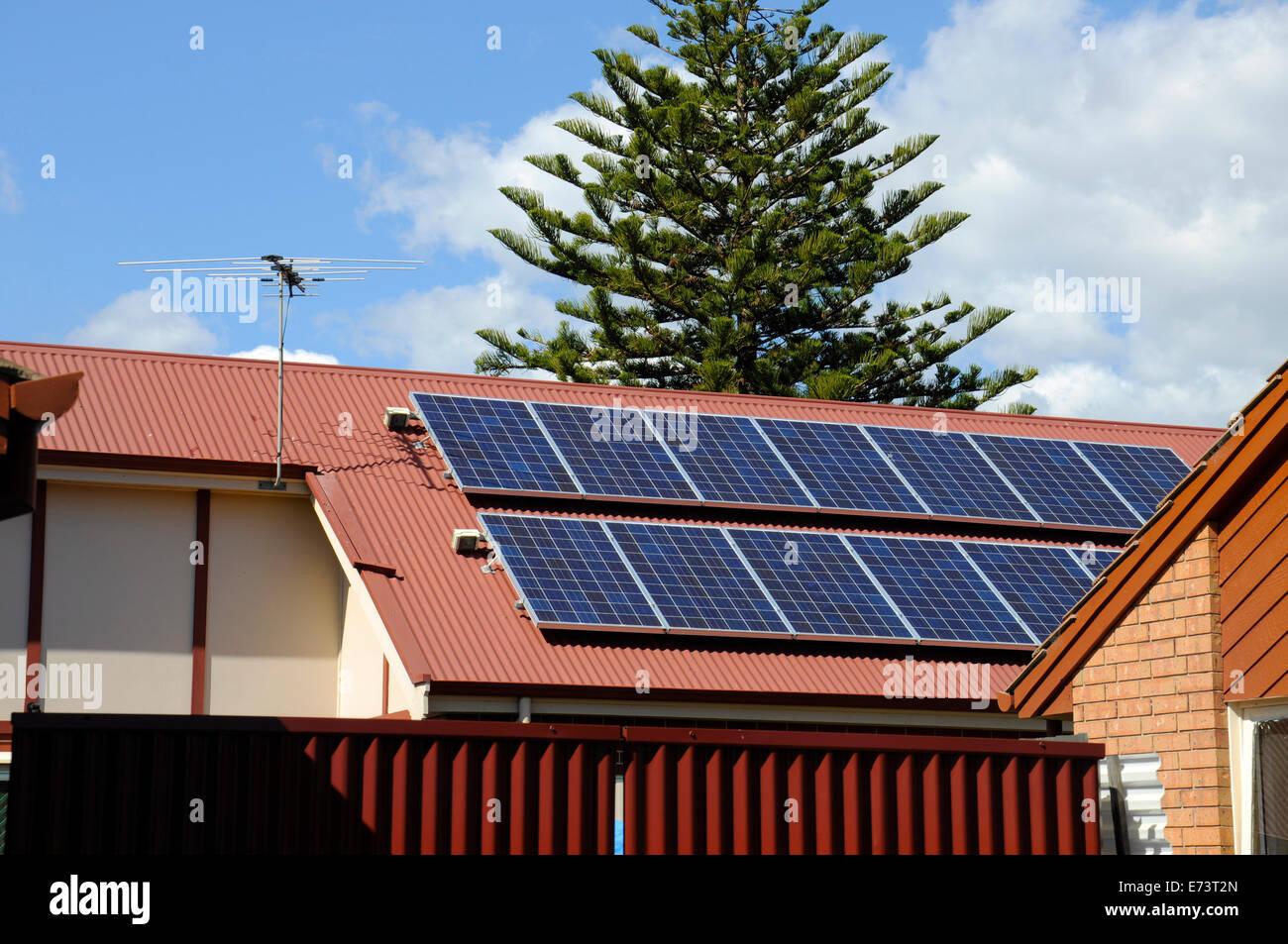 Australian photovoltaic solar power panels on a suburban rooftop. - Stock Image