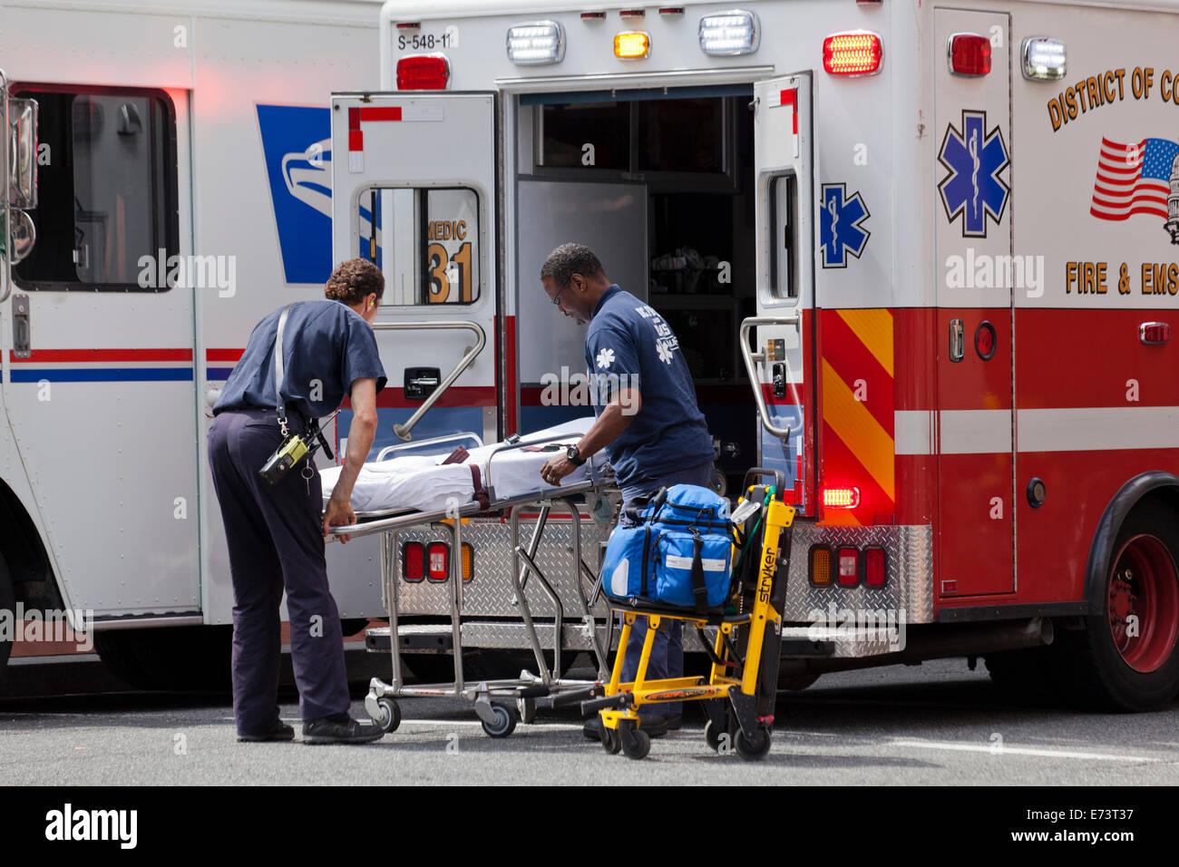 EMTs loading stretcher on EMS ambulance - Washington, DC USA Stock Photo