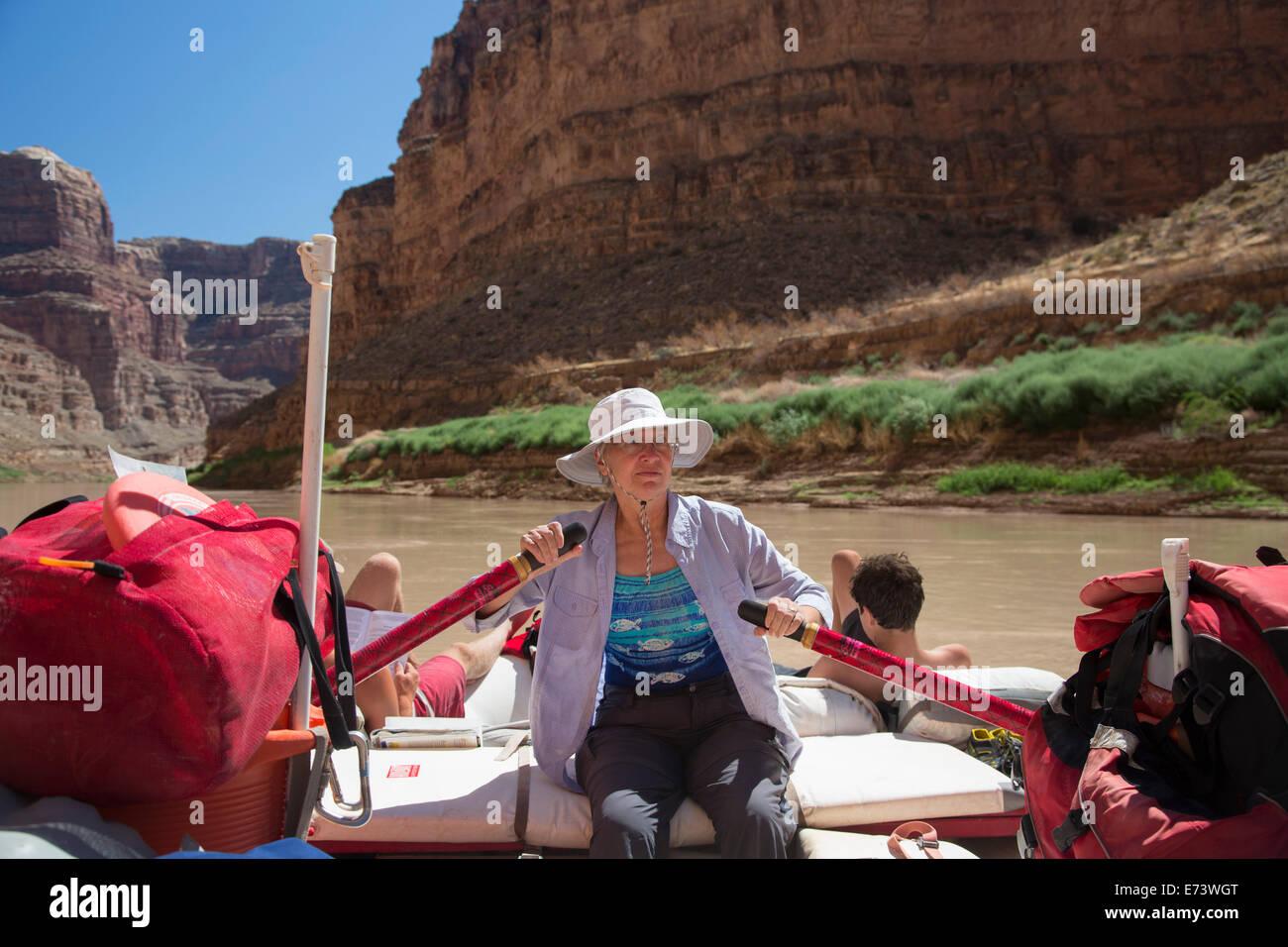 Canyonlands National Park, Utah - Susan Newell, 65, rows a raft on the Colorado River through Cataract Canyon. - Stock Image
