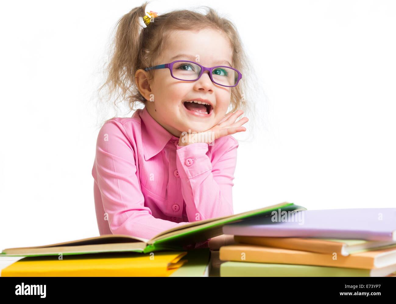 Funny kid girl in glasses reading books - Stock Image