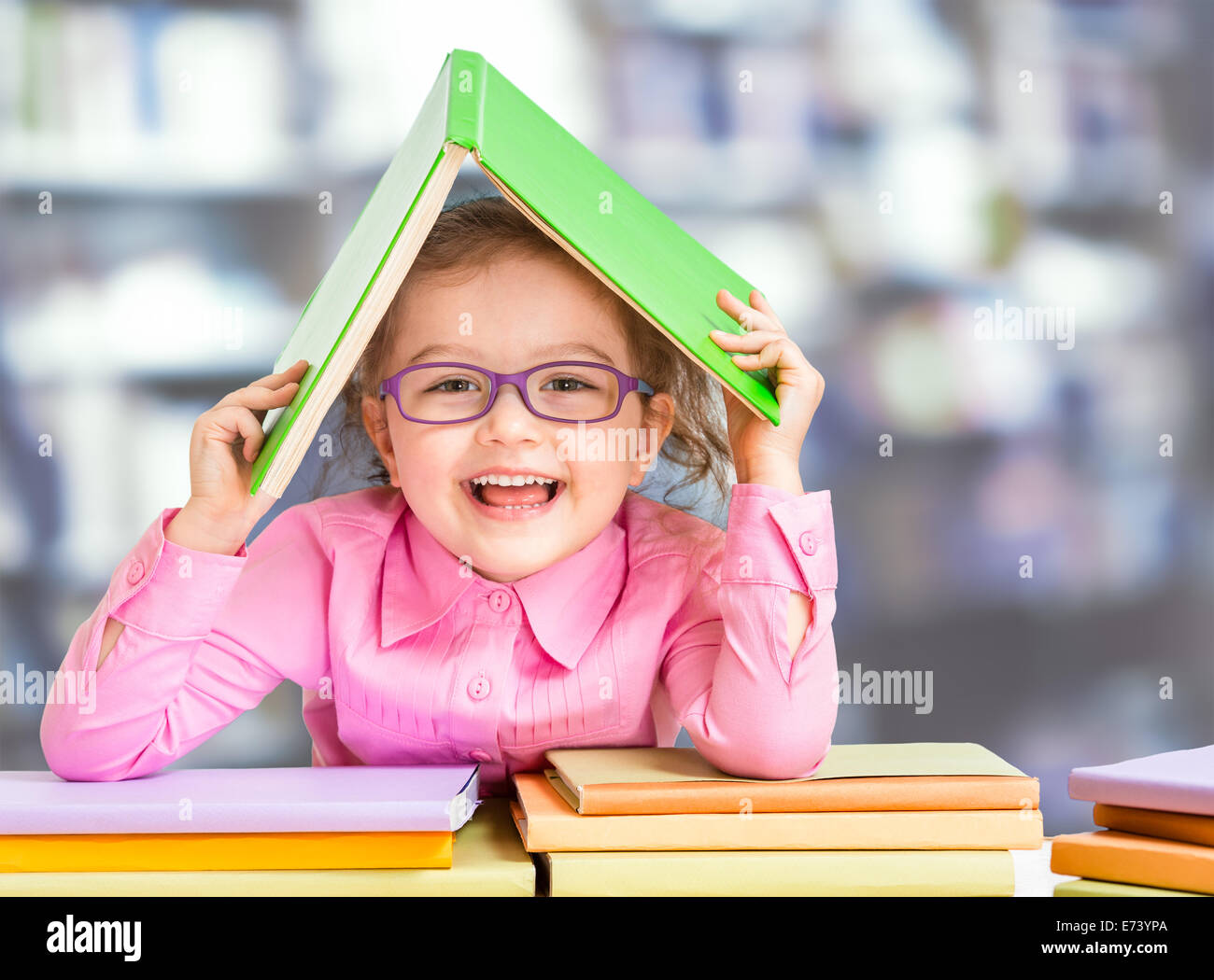 Little girl in glasses under roof made from book. - Stock Image