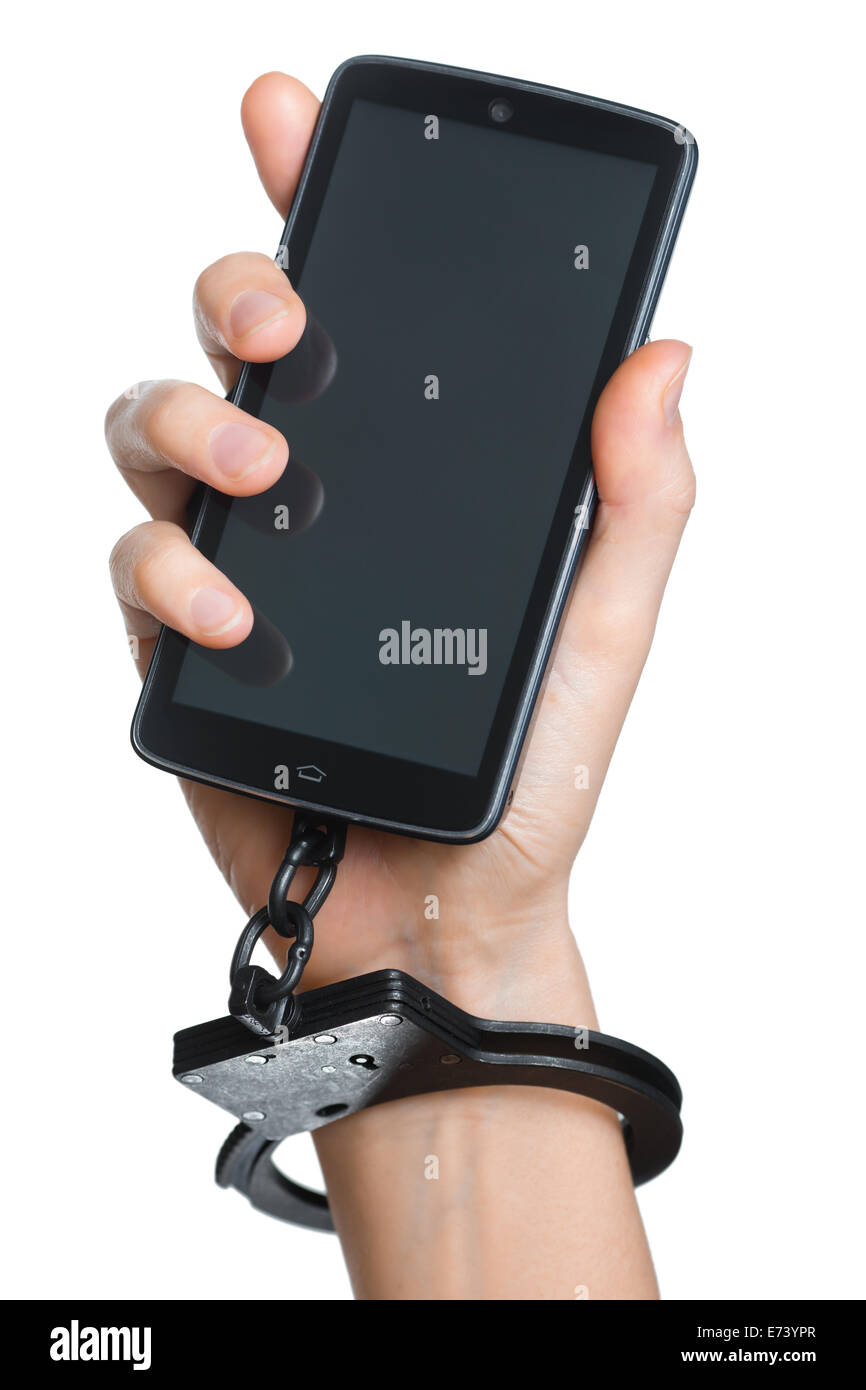 Mobile phone addiction concept. Smartphone and handcuff in hand isolated on white. - Stock Image