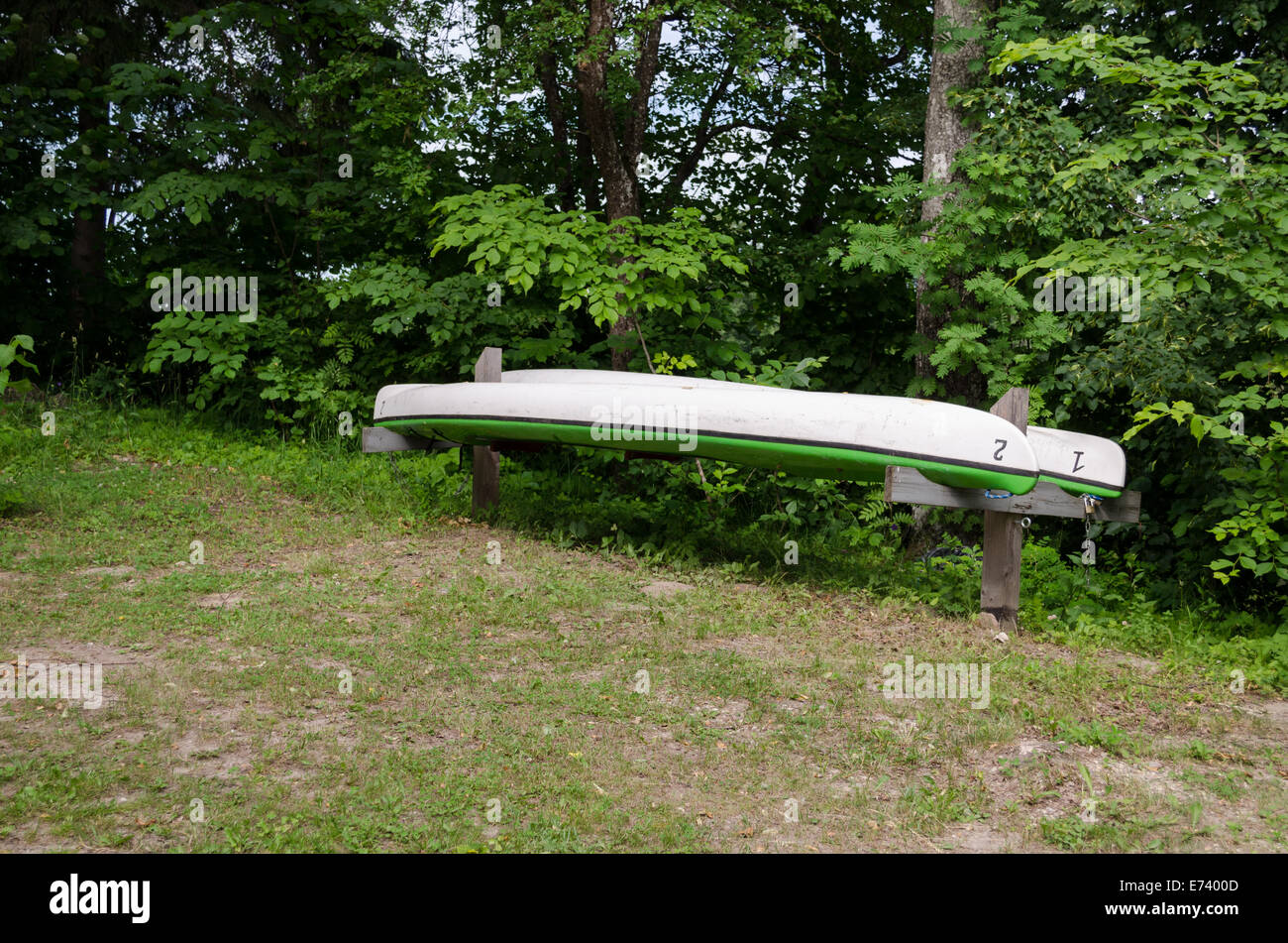 inverted two green canoes on wooden sticks dug into the ground - Stock Image