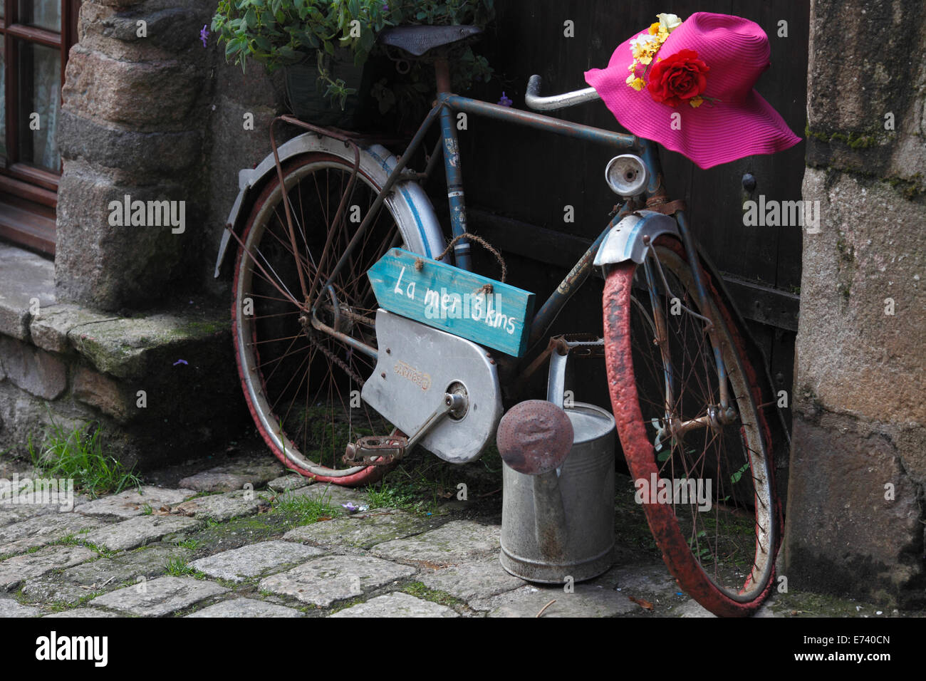 bike with a sign to the Sea, flowers and a pink hat on the handlebars. - Stock Image