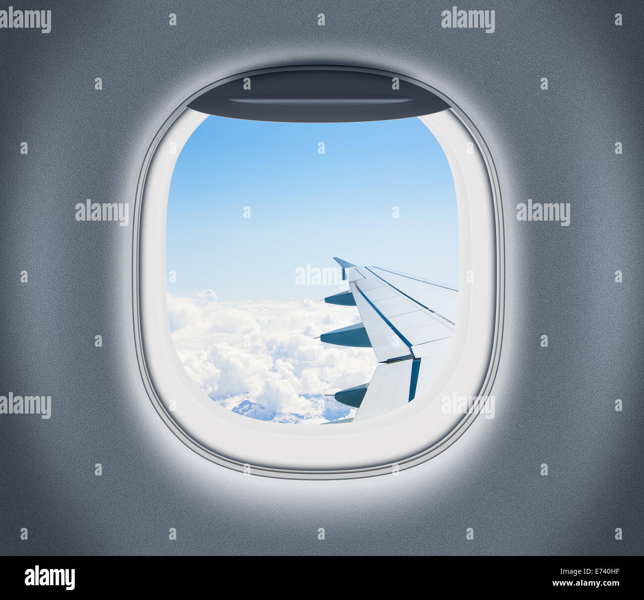 Airplane or aeroplane window with wing and cloudy sky behind. Air travel and flight concept. - Stock Image