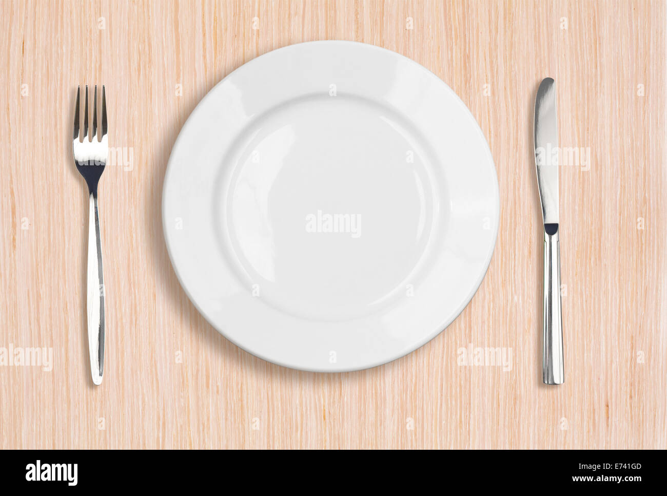 white plate, knife and fork top view on wooden table - Stock Image