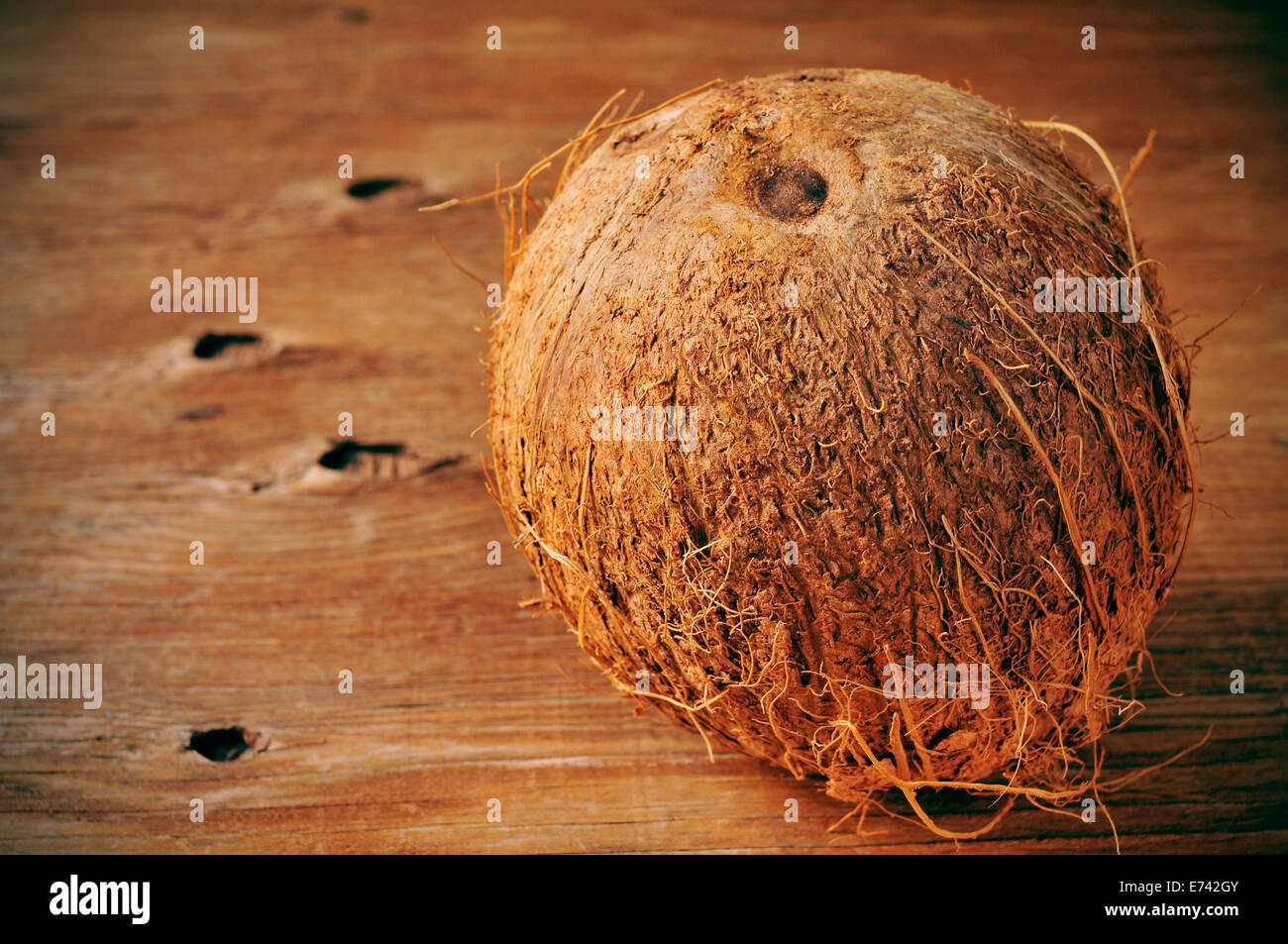 a coconut on a rustic wooden table - Stock Image