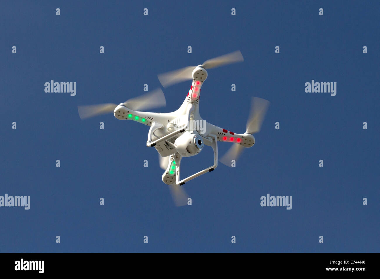 small unmanned helicopter with a camera floating in the blue sky - Stock Image