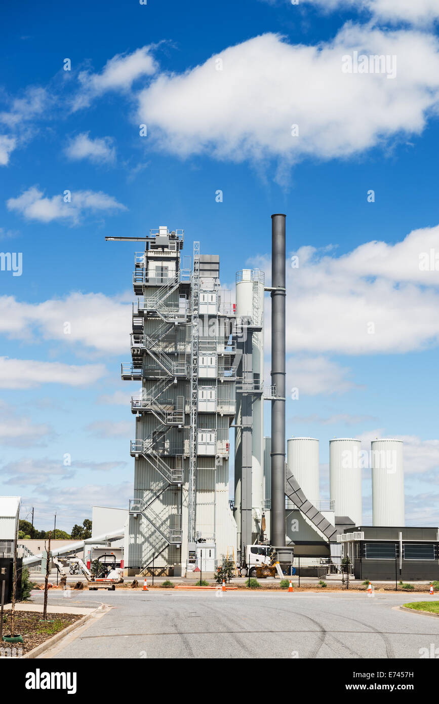 Modern industrial building of manufacturing plant against blue sky - Stock Image