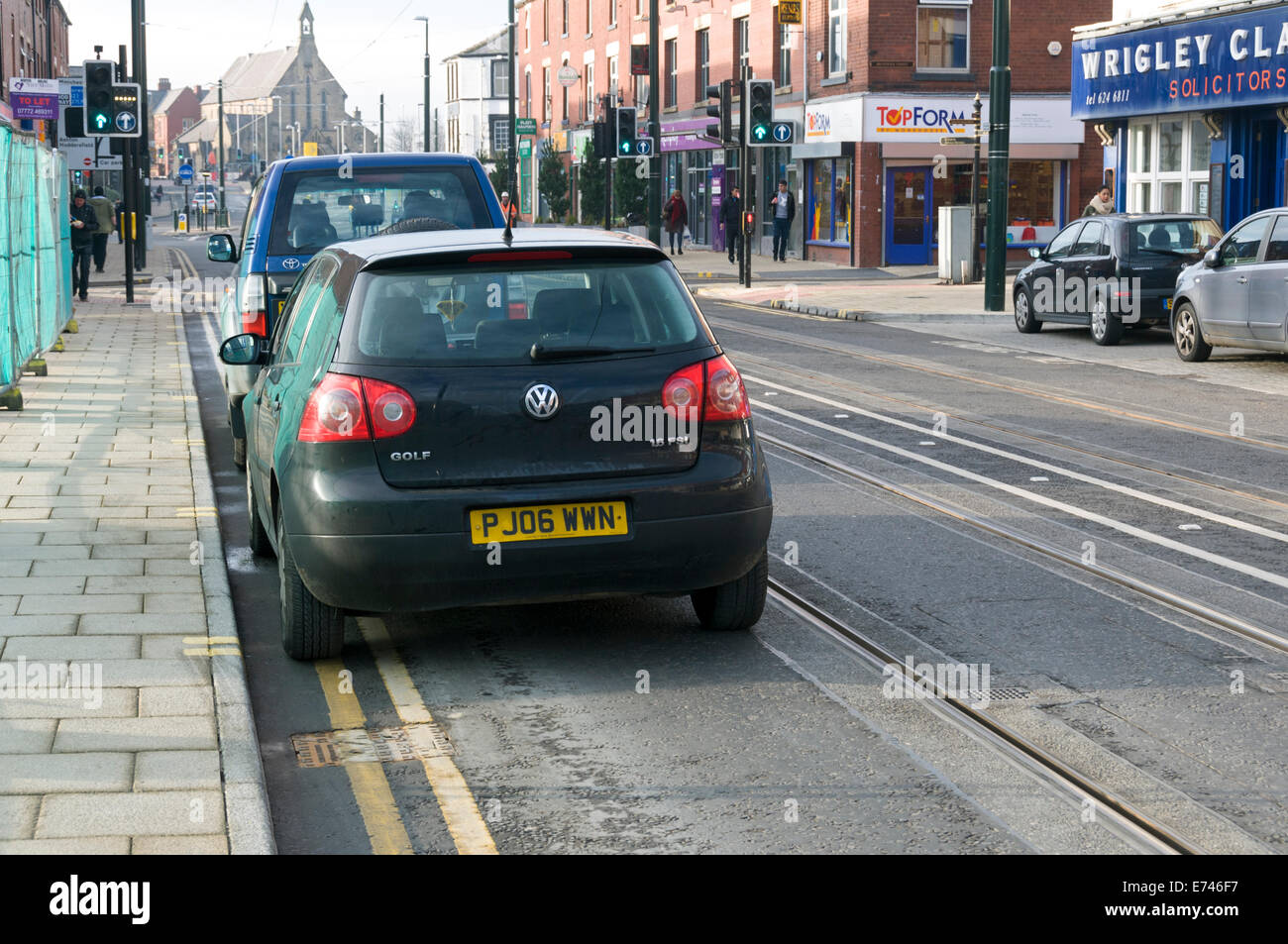Two vehicles parked illegally and blocking the tram track, Union Street, Oldham, Greater Manchester, England, UK. - Stock Image