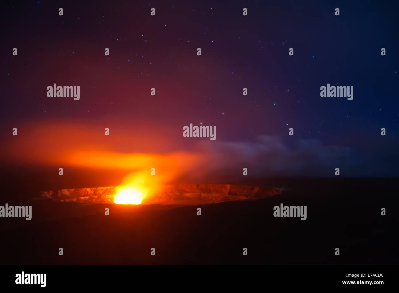 The Kilauea Magma chamber glowing below a night sky with stars. - Stock Image