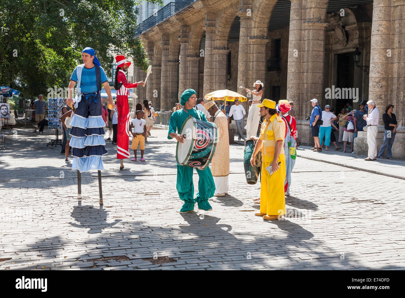 Street entertainers including performers on stilts and playing a big drum at Plaza de Armas, downtown Havana, Cuba - Stock Image