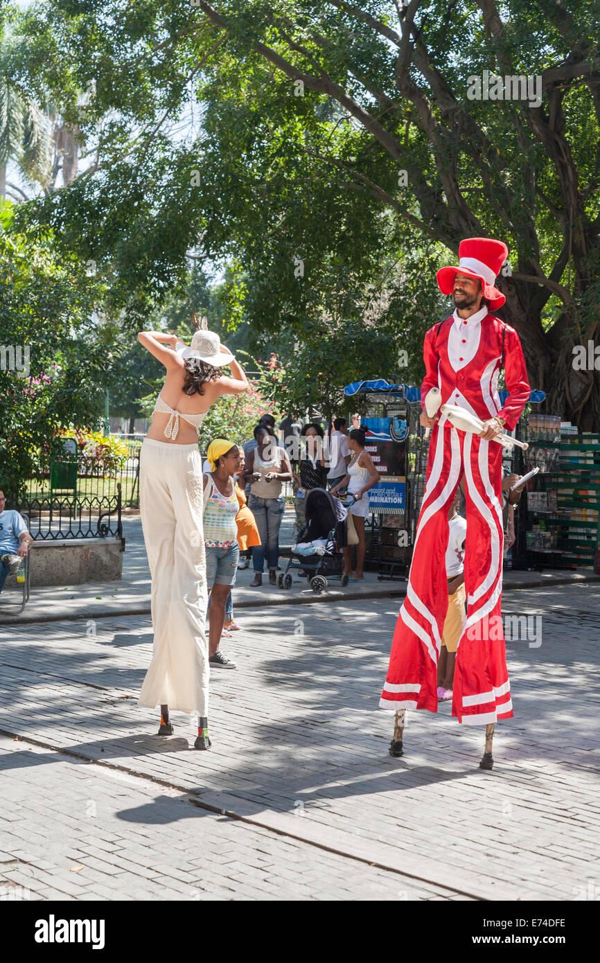 Street entertainers on stilts at Plaza de Armas, downtown Havana, Cuba - Stock Image