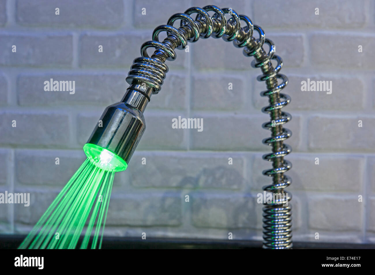 Ornate illuminated luxury tap faucet with green light and water ...
