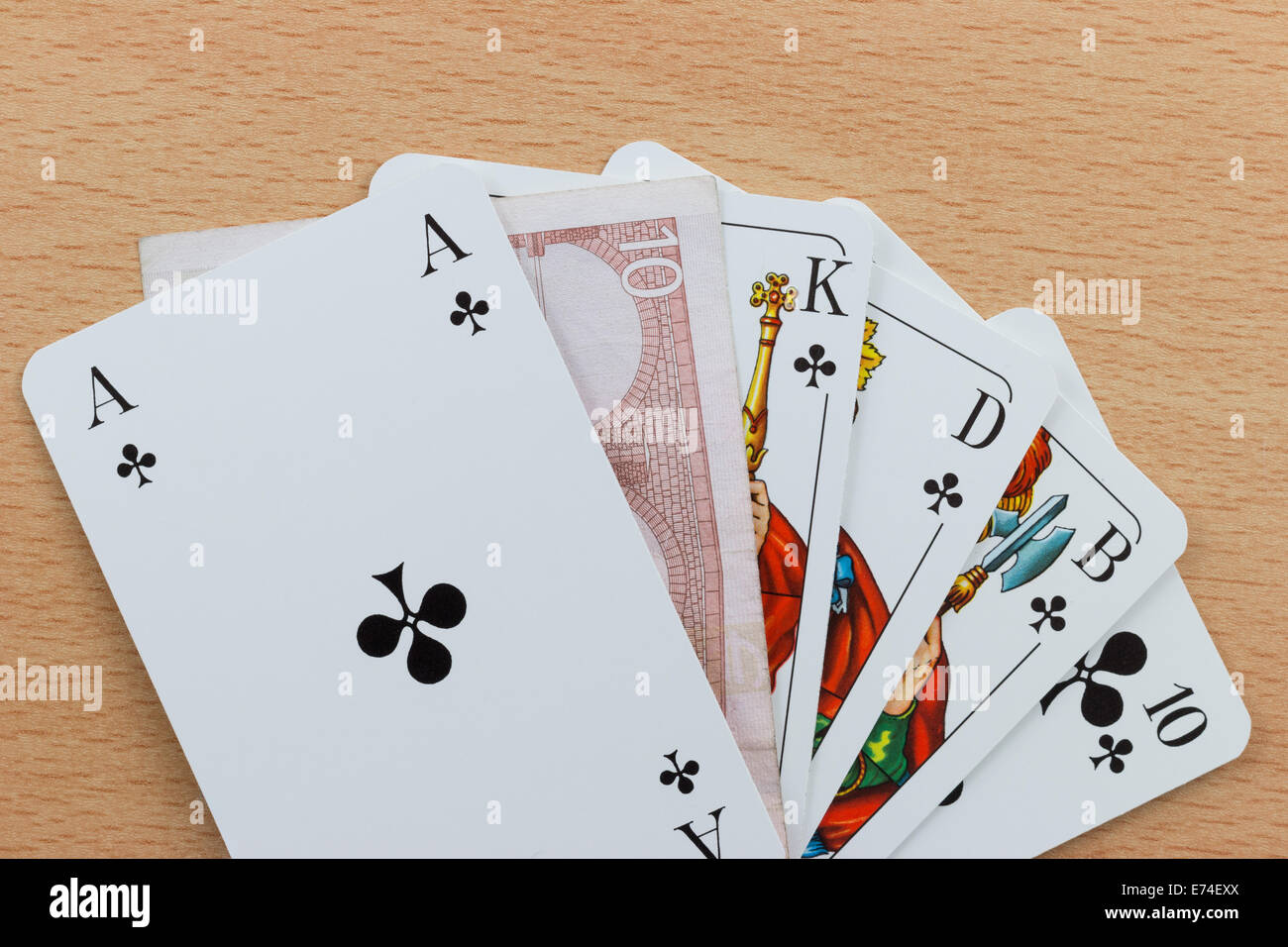 Deck of poker cards showing a Royal Flush with a Euro note - Stock Image