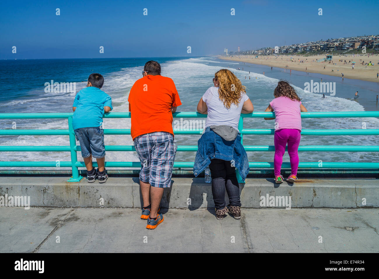 A vacationing family leans on the railing at the Manhattan Beach municipal pier and look out to sea. - Stock Image