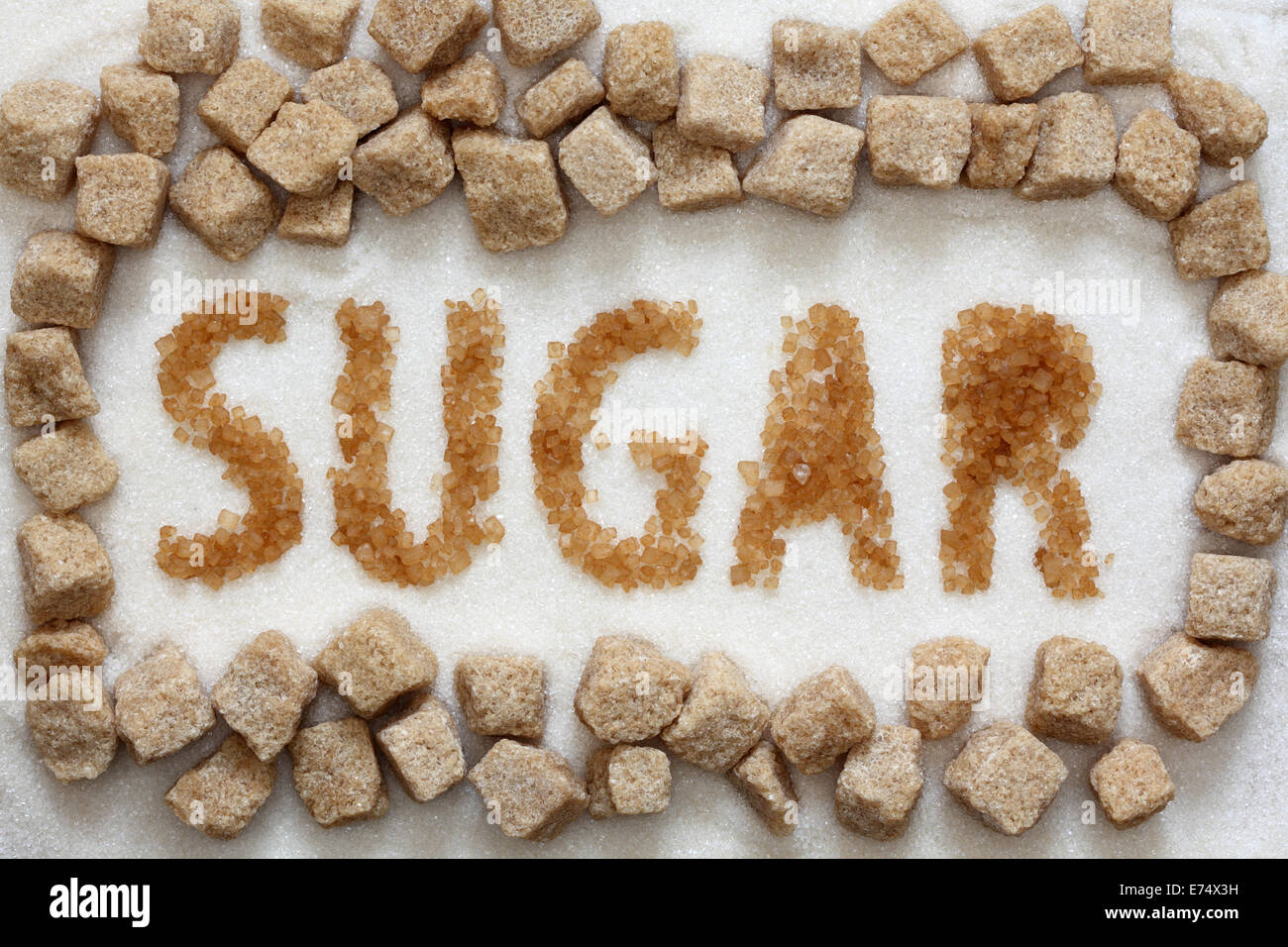 The word 'sugar' written with sugar cane on white sugar background and brown cane sugar cubes. Close-up. - Stock Image